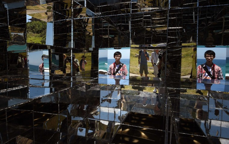 """A man looks into a mirrored sculpture by artist Neon titled """"House of mirrors"""" overlooking Sydney's coastline as artists from 16 countries prepare their works for the upcoming Sculpture by the Sea exhibition (William West/AFP/Getty Images)"""