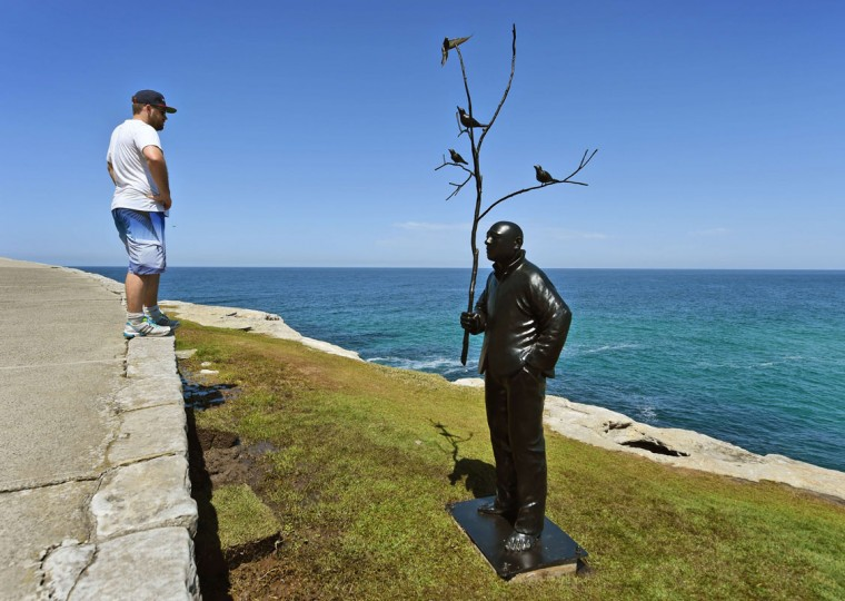 """A man looks at a sculpture by artist Wang Shugang of China titled """"man playing with birds"""" overlooking Sydney's coastline as artists from 16 countries prepare their works for the upcoming Sculpture by the Sea exhibition, on October 23, 2014. (William West/AFP/Getty Images)"""