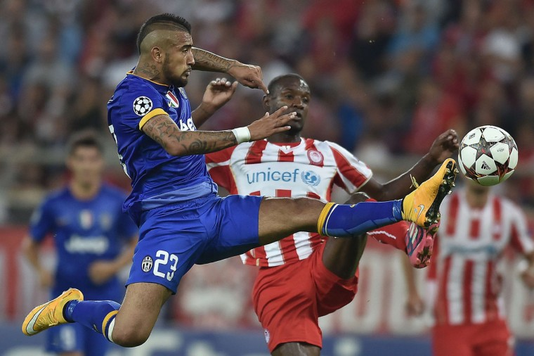 Juventus' Arturo Vidal, left, fights for the ball with Olympiacos' Eric Abidal during the Group A Champions League football match at the Karaiskaki stadium in Athens' Piraeus district on October 22, 2014. (ARIS MESSINIS/AFP/Getty Images)