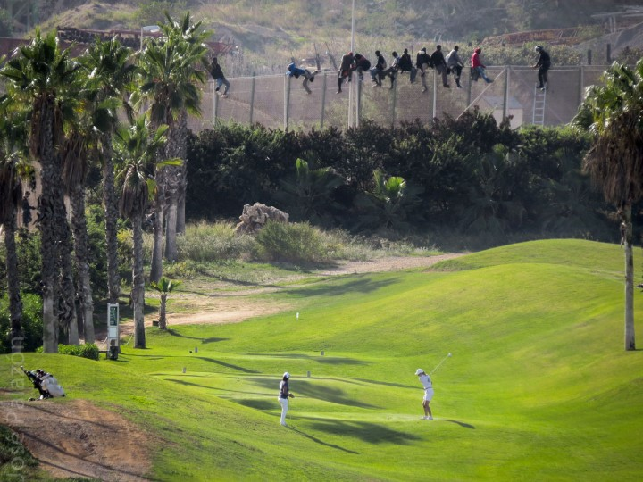 This handout picture released on October 22, 2014 by local humanitarian group Prodein shows golfers playing from a fairway back-dropped by African migrants sitting atop a border fence during an attempt to cross into the Spanish north African enclave of Melilla. (JOSE PALAZON OSMA/AFP/Getty Images)
