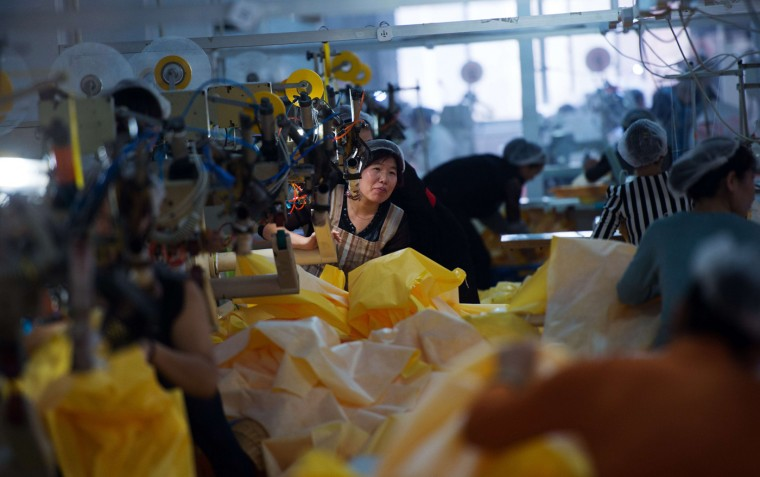 This photo taken on October 23, 2014 in Anqiu, some 500 kilometers south of Bejing, shows women working on the CT1SL428, a protective suit for use in handling people infected with the Ebola virus, in a sewing room of Lakeland Industries Inc. Lakeland, a global manufacturer of industrial protective clothing, produces suits to be worm by healthcare workers and others being exposed to Ebola. (Johannes Eisele/AFP/Getty Images)