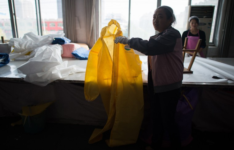 Women work on the CT1SL428, a protective suit for use in handling people infected with the Ebola virus, in a sewing room of Lakeland Industries Inc. in Anqiu, some 500 kilometers south of Bejing, on October 24, 2014. Lakeland, a global manufacturer of industrial protective clothing, produces suits to be worm by healthcare workers and others being exposed to Ebola. (Johannes Eisele/AFP/Getty Images)