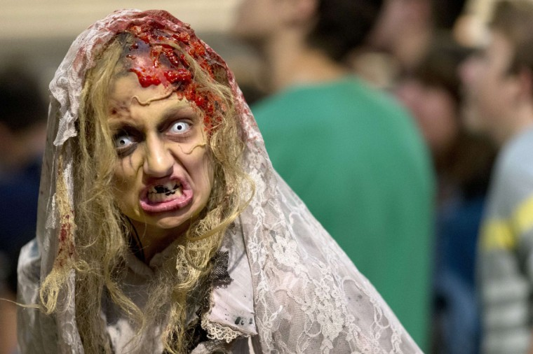 "A woman dressed as a zombie entertains people waiting on October 30, 2014 to see the show ""la Peste"" at the Manoir de Paris haunted house in Paris. (Kenzo Tribouillard/AFP/Getty Images)"
