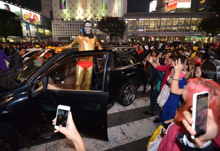 People wear costumes as they pose for pictures while taking part in a Halloween parade in Tokyo on October 31, 2014. Tens of thousands of people gathered at Tokyo's Shibuya fashion district to celebrate Halloween. (Yoshikazu Tsunoyo/AFP/Getty Images)