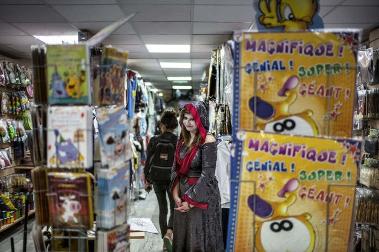An employee wearing a costume stands in a fancy dress store on Halloween on October 31, 2014 in Oullins, central-eastern France. (Jeff Pachoud/AFP/Getty Images)