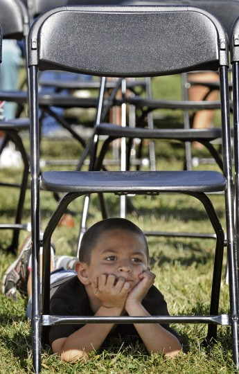 Michael Angelo, 5, of Pennsville, N.J., finds shade under a chair at the main stage as he and his family watched his mother compete in the Giant & Phillips Seafood Ultimate Crab Challenge during the 43rd Maryland Seafood Festival at Sandy Point State Park in September 2010.