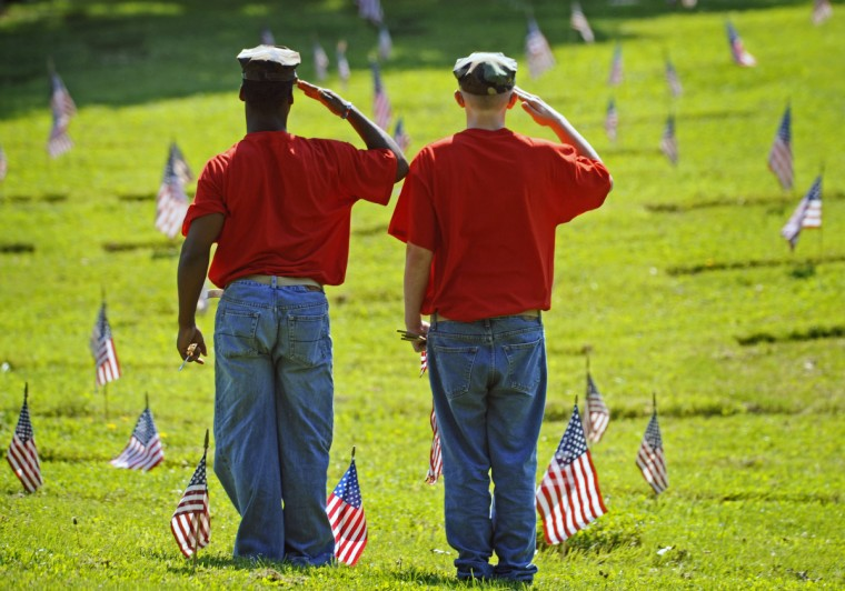 About 45 members of the Historic Elkridge Young Marines and the Harford County Young Marines placed about 3,500 American flags on the graves of veterans at the Dulaney Valley Memorial Gardens in advance of the Memorial Day ceremony on Monday. Devonta Brown, left, of Abingdon, and Brandon Mineer, of Aberdeen, salute after placing an American flag at one of the grave site in May 2009. (Kenneth K. Lam/Baltimore Sun)