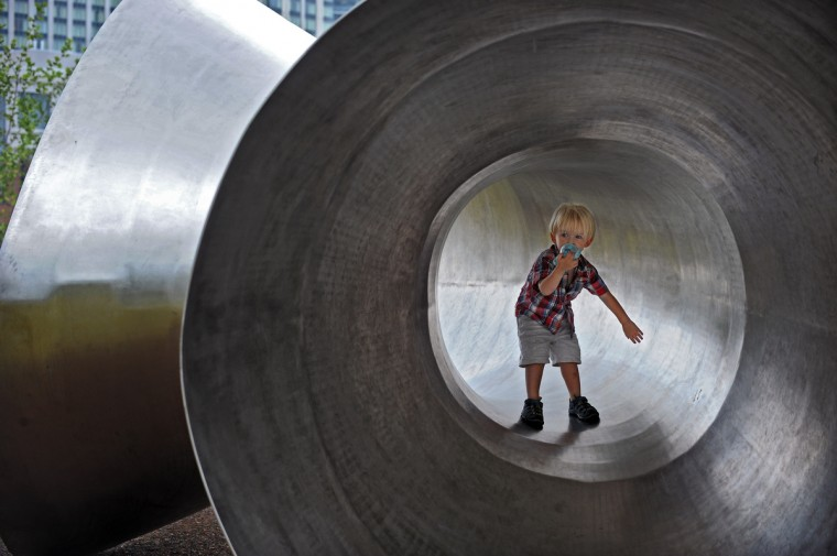 City resident Joseph Wetherell, 2, enjoys the weather while playing in an outdoor sculpture at Pierce's Park near Pier Five of Inner Harbor in June 2012. (Kenneth K. Lam/Baltimore Sun)