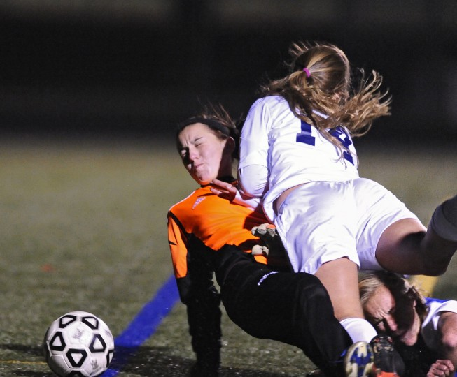 Catonsville's Deanna Eveland, right, collides with Sparrows Point goalie Madison Anthony in the first half of their Baltimore County girls soccer championship game in October 2013. (Kenneth K. Lam/Baltimore Sun)