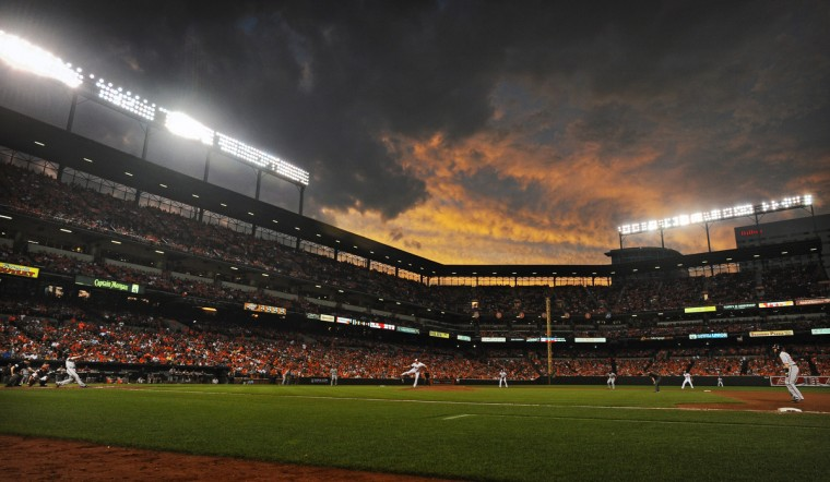 As the sun sets at Camden Yards, the Nationals' Adam LaRoche hits a sacrifice fly ball with the bases loaded, driving in a run in the fifth inning. (Kenneth K. Lam/Baltimore Sun)