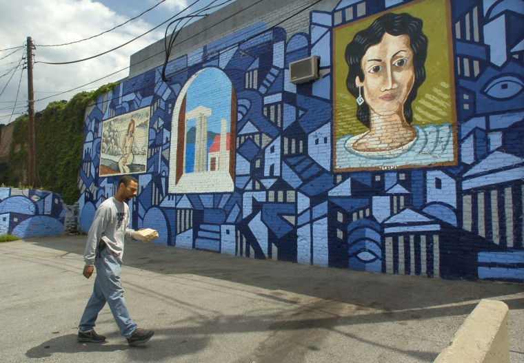 7/21/01: Thomas Green, a longshoreman who works nearby, walks by a new mural on S. Oldham St., which frames the lot for the St. Nicholas Greek Orthodox Church. The mural, unveiled on June 11, was a joint project between the city and the Greektown Community Development Corp. (Amy Davis/Baltimore Sun)