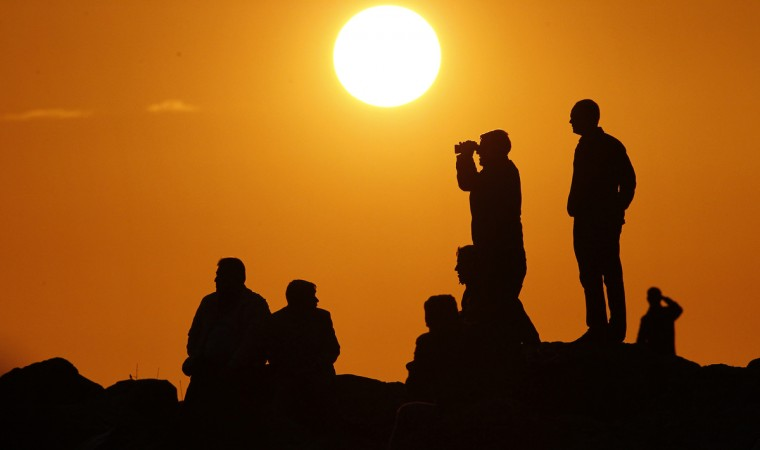 People are silhouetted on the top of a hill close to the border line between Turkey and Syria near Mursitpinar bordergate as they watch the U.S led airstrikes over the Syrian town of Kobani in Sanliurfa, Turkey. Kurdish fighters in Syrian city of Kobani have pushed back Islamic State militants in a number of locations as U.S. airstrikes on ISIS positions continue in and around the city. Since mid-September more than 200,000 people from Kobani flee into Turkey. (Gokhan Sahin/Getty Images)