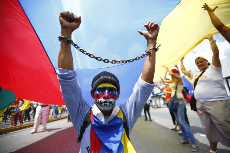 Opposition supporters take part in a march against the government of Nicolas Maduro in Caracas. Venezuela's government and political opposition marched through the capital Caracas on Saturday. Supporters of Socialist President Maduro protested this month's killing of a young 'Chavista' lawmaker, a crime the government has blamed on political opponents, including Colombian paramilitary forces. Separately, the opposition demonstrated against a laundry list of issues, including a slumping economy, shortages of basic goods, and sky-high crime rates. (Jorge Silva/Reuters)