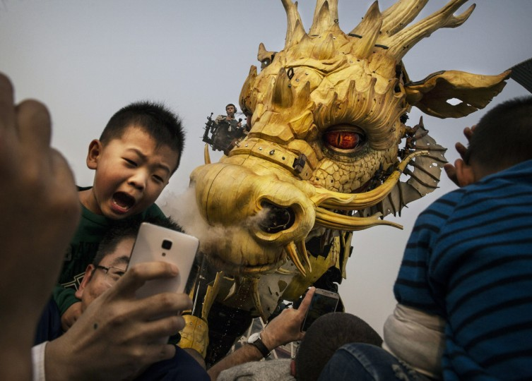 "A Chinese boy reacts as he sits on his father's shoulders as a large mechanical dragon called ""Dragon Horse"" that is part of the Long Ma Performance by the French company La Machine comes close and sprays water at the National Stadium in Beijing, China. The event was held to mark 50 years of diplomatic relations between France and China. (Kevin Frayer/Getty Images)"