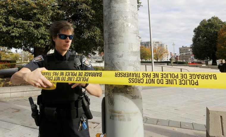 A police officer closes off the scene near the Canada War Memorial following a shooting incident in Ottawa October 22, 2014. A Canadian soldier was shot at the Canadian War Memorial and a shooter was seen running towards the nearby parliament buildings, where more shots were fired, according to media and eyewitness reports. (Chris Wattie/Reuters)