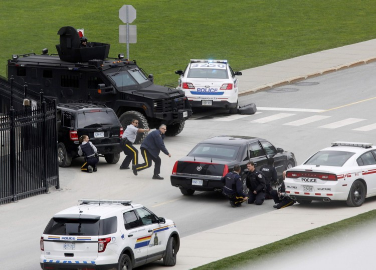 Police officers take cover near Parliament Hill following a shooting incident in Ottawa October 22, 2014. A Canadian soldier was shot at the Canadian War Memorial and a shooter was seen running towards the nearby parliament buildings, where more shots were fired, according to media and eyewitness reports. (Chris Wattie/Reuters)