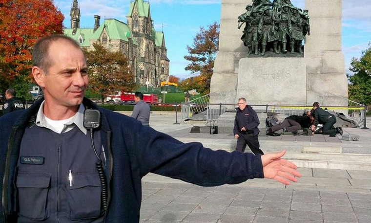 A police officer holds back the public from Canada's National War Memorial as CPR is performed on a shooting victim in Ottawa October 22, 2014. A gunman shot and wounded a soldier in Ottawa and then entered the country's parliament buildings chased by police, with at least 30 shots fired, according to media and eyewitness reports on Wednesday. (Bill Curry/The Globe and Mail)