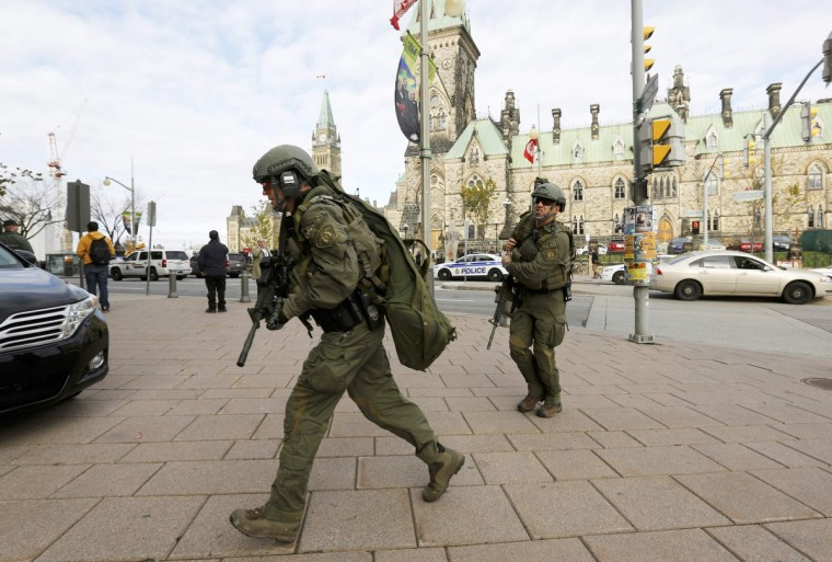 Armed RCMP officers head towards the Langevin Block on Parliament Hill following a shooting incident in Ottawa October 22, 2014. A Canadian soldier was shot at the Canadian War Memorial and a shooter was seen running towards the nearby parliament buildings, where more shots were fired, according to media and eyewitness reports.(Chris Wattie/Reuters)