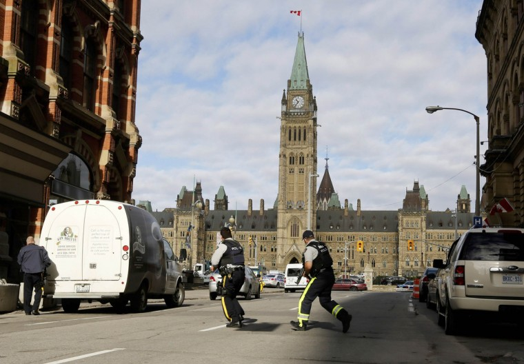 Armed RCMP officers race across a street on Parliament Hill following a shooting incident in Ottawa October 22, 2014. A Canadian soldier was shot at the Canadian War Memorial and a shooter was seen running towards the nearby parliament buildings, where more shots were fired, according to media and eyewitness reports. (Chris Wattie/Reuters)