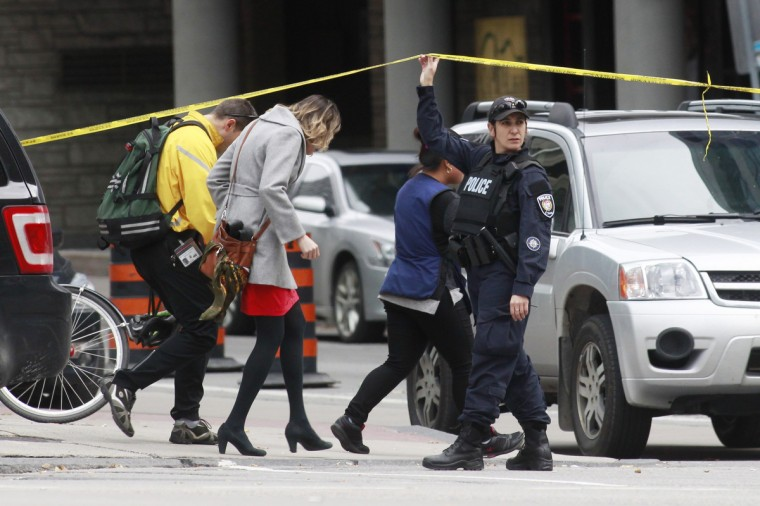 A Ottawa police officer holds up a length of police tape for pedestrians leaving the downtown area following shooting incidents in Ottawa October 22, 2014. A Canadian soldier was shot at the National War Memorial in downtown Ottawa and a gunman was shot and killed in a nearby parliament building, media and witnesses reported. (Blair Gable/Reuters)