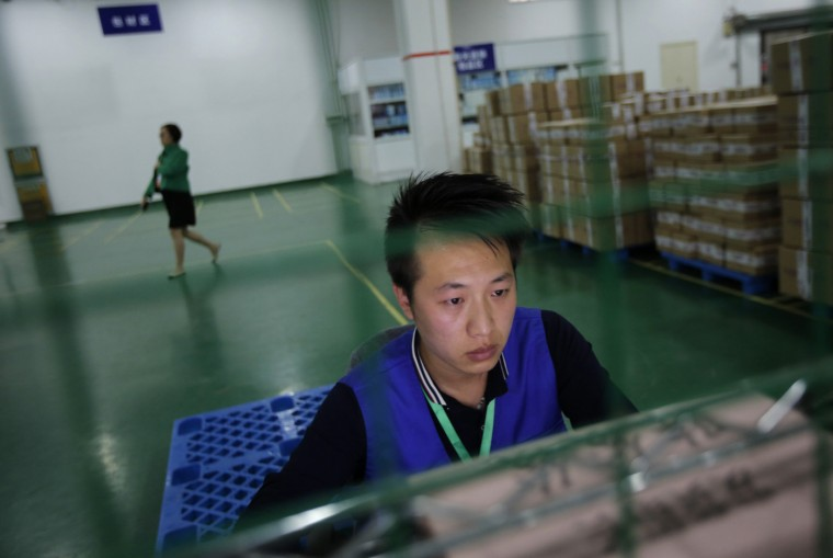 "An employee works at an Alibaba Group warehouse on the outskirts of Hangzhou, Zhejiang province October 30, 2014. A trademark spat between Chinese e-commerce giant Alibaba Group Holding Ltd and rival JD.com flared into public view after JD published an Alibaba letter urging publishers to be careful about advertising in promotions for China's annual ""Singles' Day"" spree, the world's largest online shopping day. REUTERS/Carlos Barria"