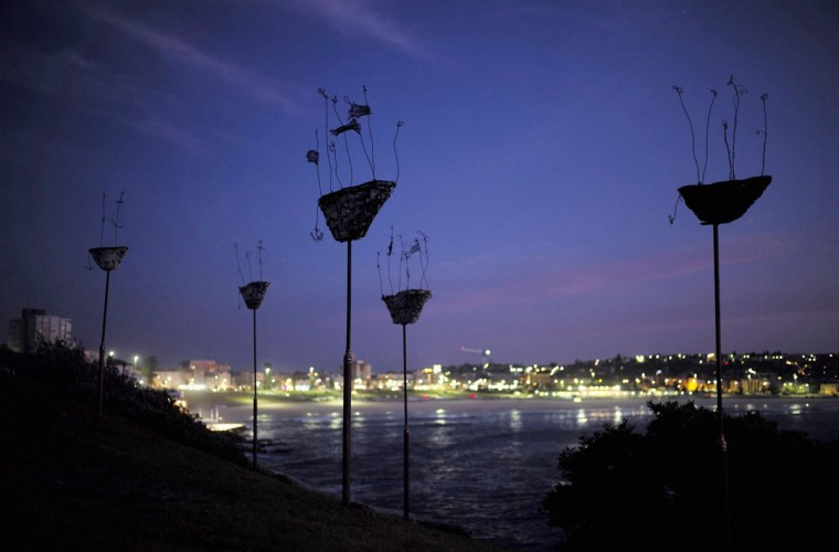 """A sculpture by Melissa McElhone titled 'Vessels of destiny' is shown before sunrise as part of the """"Sculpture by the Sea"""" exhibition at Sydney's Bondi Beach on its opening day October 23, 2014. (Jason Reed/Reuters)"""