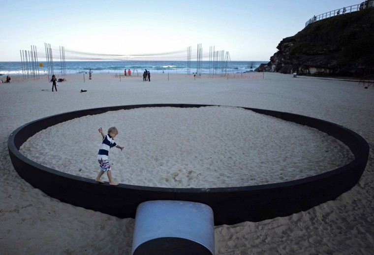 """A boy runs along the rim of a giant frying pan sculpture by Andrew Hankin titled 'We're frying out here' as part of the """"Sculpture by the Sea"""" exhibition at Sydney's Tamarama Beach. (Jason Reed/Reuters)"""