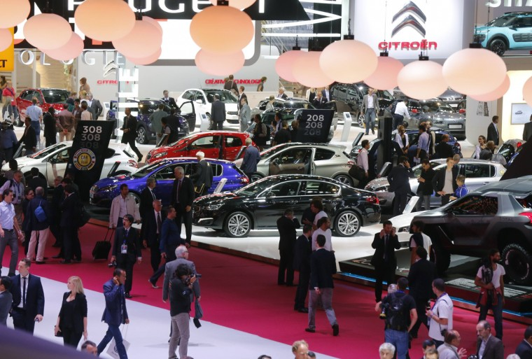 A general view shows visitors walking past Peugeot and Citroen cars on media day at the Paris Mondial de l'Automobile, October 2, 2014. The Paris auto show opens its doors to the public from October 4 to October 19. Jacky Naegelen/Reuters photo
