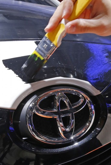 An artist paints a Toyota car displayed on media day at the Paris Mondial de l'Automobile, October 2, 2014. The Paris auto show opens its doors to the public from October 4 to October 19. Jacky Naegelen/Reuters photo