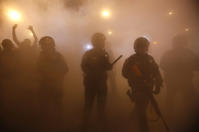 Police officers walk through smoke from a bonfire during a street celebration in the Mission District, in San Francisco, California October 29, 2014. The San Francisco Giants beat the Kansas City Royals 3-2 on Wednesday to win their third World Series title in five seasons. REUTERS/Stephen Lam