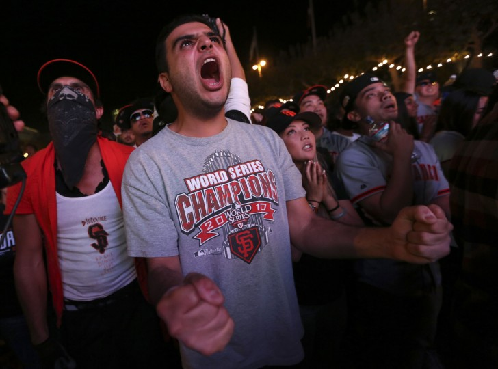 Fan Elior Ilishah celebrates during the San Francisco Giants win over the Kansas City Royals in the World Series during a television viewing event at the Civic Center in San Francisco, California October 29, 2014. REUTERS/Robert Galbraith