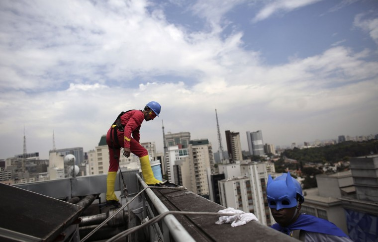 Men dressed as comic book heroes Batman and Flash prepare to clean the glass facade of Hospital Infantil Sabara before meeting with patients of the children's hospital in Sao Paulo October 7, 2014. Brazil celebrates Children's Day on October 12. (REUTERS/Nacho Doce)