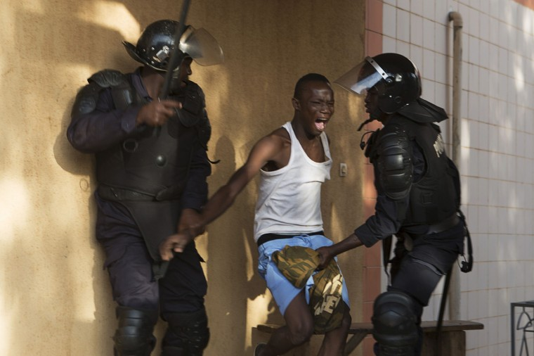 Riot police arrest an anti-government protester in Ouagadougou, capital of Burkina Faso, October 30, 2014. Thousands of protesters marched on Burkina Faso's presidential palace after burning the parliament building and ransacking state television offices on Thursday, forcing President Blaise Compaore to scrap a plan to extend his 27-year rule. Emergency services said at least three protesters were shot dead and several others wounded by security forces when the crowd tried to storm the home of Compaore's brother. Security forces also fired live rounds and tear gas at protesters near the presidency in the Ouaga 2000 neighborhood. REUTERS/Joe Penney