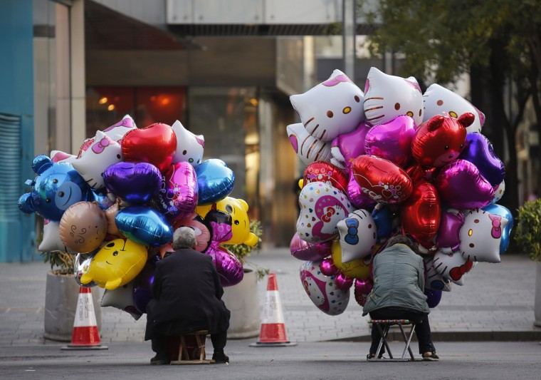 Balloon sellers wait for customers at a shopping district in Beijing October 16, 2014. (Kim Kyung-Hoon/Reuters)