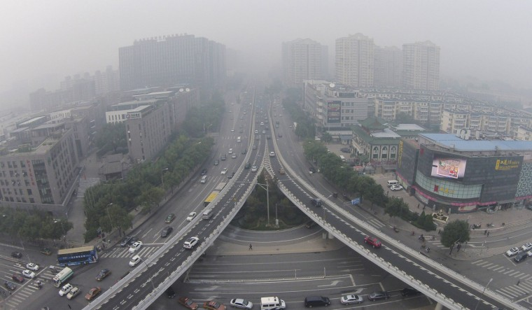 Vehicles and buildings are seen amid the heavy haze in Beijing, October 9, 2014. Beijing issued a yellow alert for air pollution on Wednesday with smog forecast to continue for the next three days until Saturday, said the Beijing heavy air pollution response office, Xinhua News Agency reported. (Jason Lee/Reuters)