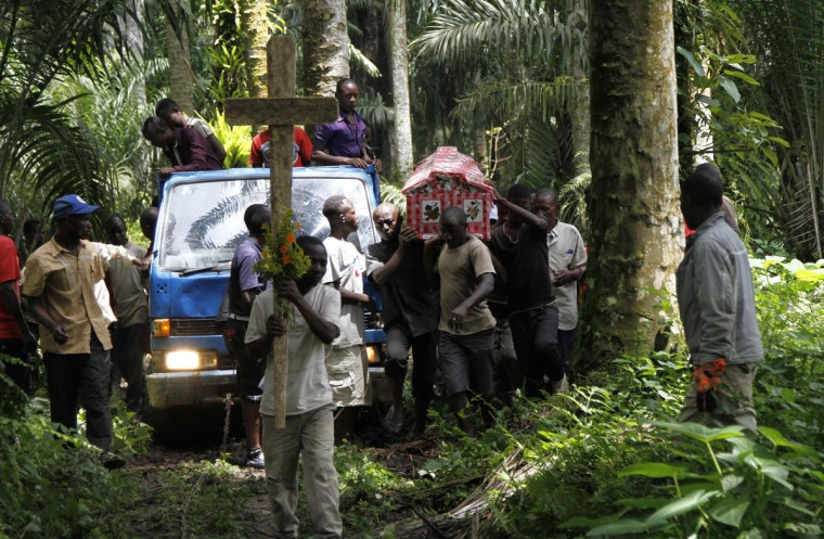 Relatives and friends carry the body of Yvonne Masika killed during an attack by suspected ADF-NALU rebels for burial in Mbau village near Beni, in North Kivu province, October 21, 2014. Suspected Ugandan rebels killed at least 23 people overnight in their second attack near the eastern Congolese town of Beni in 48 hours, the local governor said on Saturday, prompting the U.N. peacekeeping mission to call for renewed military action. (REUTERS/Kenny Katombe)