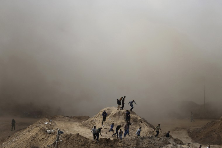 Palestinians run as smoke rises after a house is blown up during a military operation by Egyptian security forces in the Egyptian city of Rafah, on the border of the southern Gaza Strip with Egypt October 30, 2014. Egypt began clearing residents from its border with the Gaza Strip on Wednesday to create a buffer zone following some of the worst anti-state violence since President Mohamed Mursi was overthrown last year. A day after being ordered by the army to move, many in the area had already packed their belongings and begun to leave when an announcement from Cairo made the eviction official. REUTERS/Ibraheem Abu Mustafa