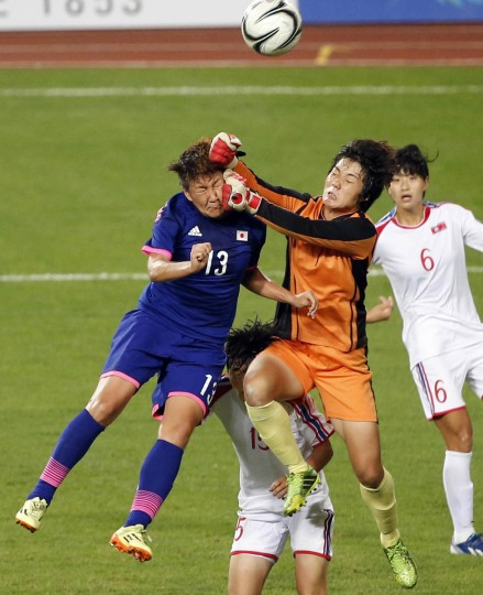 Japan's Rie Usui (Left) and North Korea's goalkeeper Hong Myong Hui fight for the ball during their women's final soccer match at the Munhak Stadium during the 17th Asian Games in Incheon. (Kim Kyung-Hoon/Reuters)
