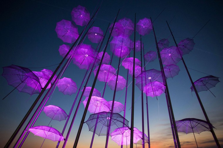 """Umbrellas"", the sculpture by Giorgos Zogolopoulos is illuminated in pink light to mark Breast Cancer Awareness Month in Thessaloniki in northern Greece October 21, 2014. (REUTERS/Alexandros Avramidis)"