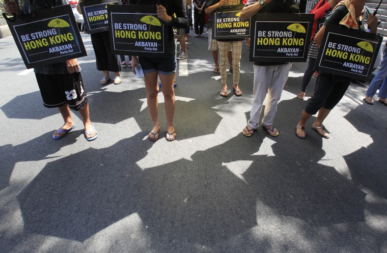 """Shadows of umbrellas are seen cast on the ground as activists protest in front of the Chinese Consular office in Makati city, metro Manila October 2, 2014. Dozens of Filipino activists demonstrated in Manila on Thursday in support of Hong Kong protesters demanding democracy in their island city. The demonstrators marched towards the Chinese consulate, toting umbrellas and placards that read """"Be strong Hong Kong"""". The pro-democracy demonstrations in Hong Kong have been dubbed the """"Umbrella Revolution,"""" after protesters held umbrellas to shield themselves from tear gas used by police last weekend to quell unrest. (Romeo Ranoco/Reuters)"""