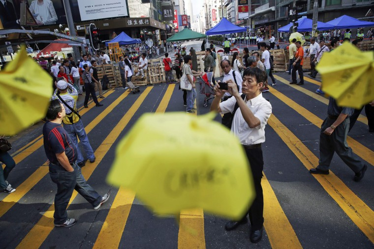 Commuters walk between barricades and miniature paper umbrellas, symbols of the pro-democracy movement, in the area occupied by protesters in Mongkok shopping district in Hong Kong October 30, 2014. A member of China's central bank's advisory body warned on Wednesday that Beijing will punish Hong Kong if pro-democracy protests that have paralyzed parts of the Chinese-controlled financial center for a month are allowed to continue. REUTERS/Damir Sagolj