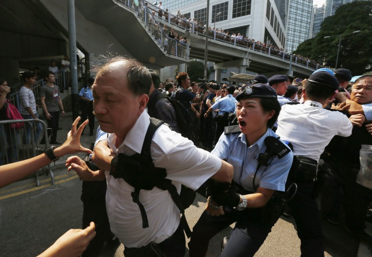 A policewoman tries to stop an anti-Occupy protester from breaking a police cordon to charge at pro-democracy protesters during a confrontation in Hong Kong October 13, 2014. Hundreds of unidentified people, some wearing masks, tried to break down protest barriers in the heart of Hong Kong's business district on Monday, scuffling with protesters who have occupied the streets for the past two weeks. (Bobby Yip/Reuters)