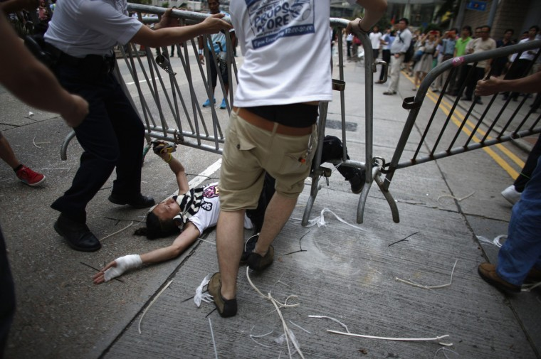 Anti-Occupy Central protesters drag a metal fence over a pro-democracy protester at the main protest site in Admiralty in Hong Kong October 13, 2014. Hundreds of unidentified people, some wearing masks, tried to break down protest barriers in the heart of Hong Kong's business district on Monday, scuffling with protesters who have occupied the streets for the past two weeks. (Carlos Barria/Reuters)