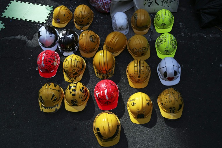 Decorated helmets, symbols of the pro-democracy movement, are left behind a barricade in the area occupied by protesters in Mongkok shopping district in Hong Kong October 30, 2014. A member of China's central bank's advisory body warned on Wednesday that Beijing will punish Hong Kong if pro-democracy protests that have paralyzed parts of the Chinese-controlled financial center for a month are allowed to continue. REUTERS/Damir Sagolj
