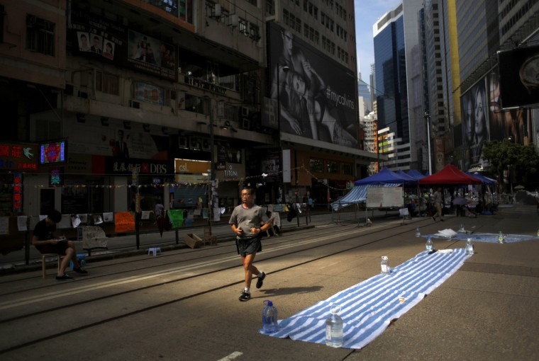 A runner jogs along a street blocked by pro-democracy protesters at the commercial area of Causeway Bay in Hong Kong October 9, 2014. Pro-democracy lawmakers demanded an investigation into Hong Kong's embattled leader Leung Chun-ying on Thursday over a $6.4 million payment he received from an Australian engineering firm while in office. The controversy ratchets up the pressure on the pro-Beijing leader just days after tens of thousands of people occupied the streets of the Asian financial center to demand greater democracy and call for Leung to step down. (Carlos Barria/Reuters)