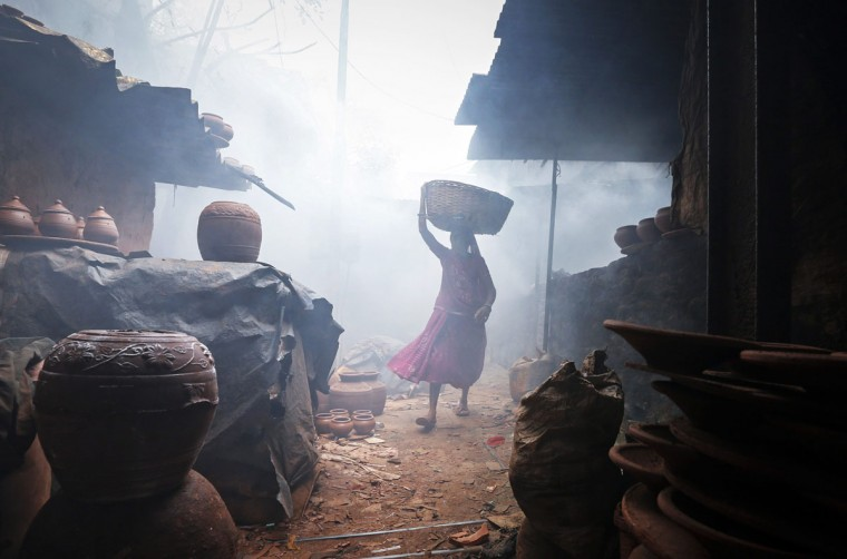 A woman potter carries earthen pots through traditional pottery kilns in Dharavi, one of Asia's largest slums, in Mumbai October 7, 2014. (REUTERS/Shailesh Andrade)