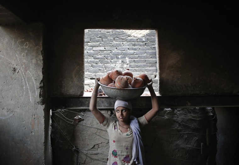 A potter carries a basket filled with clay money boxes at a workshop ahead of the Hindu festival of Diwali in New Delhi October 16, 2014. Earthen goods are sold in large numbers during Diwali, the annual Hindu festival of lights, as people use them to decorate their homes. The Diwali festival will be observed this year on October 23. (Anindito Mukherjee/Reuters)