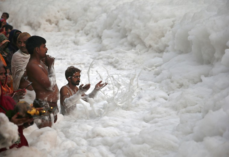 A Hindu devotee pushes the foam away to make space for other devotees to worship the Sun god Surya in the polluted waters of the river Yamuna during the Hindu religious festival of Chatt Puja in New Delhi October 30, 2014. Hindu women fast for the whole day for the betterment of their family and the society during the festival. REUTERS/Ahmad Masood