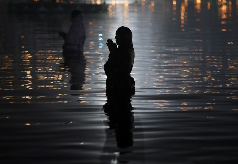 Hindu women worship the Sun god Surya in the waters of the Sun lake during the Hindu religious festival of Chatt Puja in the northern Indian city of Chandigarh October 30, 2014. Hindu women fast for the whole day for the betterment of their family and the society during the festival. REUTERS/Ajay Verma