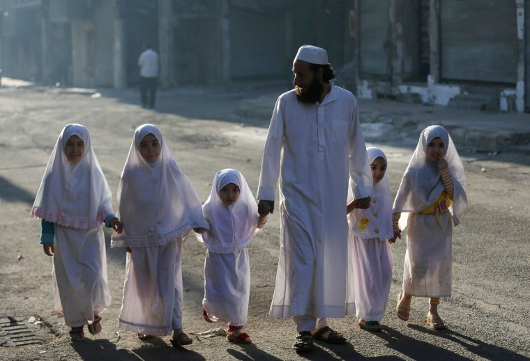 Children, accompanied by their father, walk together ahead of performing prayers on the first day of Eid al-Adha in the Duma neighbourhood in Damascus October 4, 2014. Muslims around the world celebrate Eid al-Adha to mark the end of the haj pilgrimage by slaughtering sheep, goats, camels and cows to commemorate Prophet Abraham's willingness to sacrifice his son, Ismail, on God's command. (Bassam Khabieh/Reuters)
